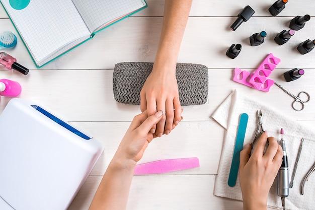 Pielęgnacja paznokci zbliżenie kobiecych rąk składanie paznokci profesjonalnym pilnikiem do paznokci w górnej części salonu piękności ...