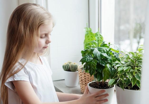 Pielęgnacja roślin doniczkowych, mała dziewczynka opiekująca się roślinami doniczkowymi