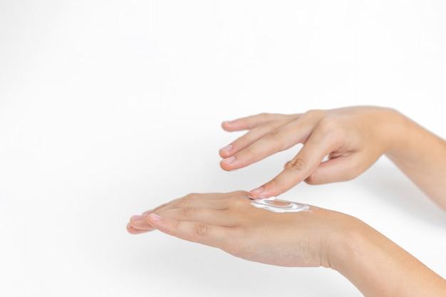 Pielęgnacja skóry dłoni. zbliżenie na rękach kobiety, stosując krem nawilżający do rąk. krem do rąk i leczenia.