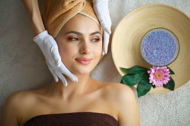 Pielęgnacja skóry i ciała. close-up młodej kobiety pierwsze leczenie spa w salonie piękności. masaż twarzy spa. zabiegi kosmetyczne na twarz. salon spa