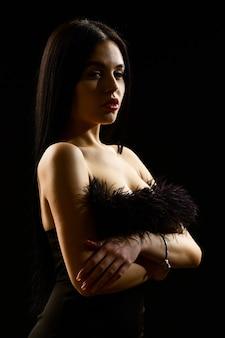Pielęgnacja skóry i makijaż. ładna czarna sukienka. młoda piękna kobieta nosić czarną suknię wieczorową. dziewczyna z nagimi ramionami pozowanie na czarnym tle. portret elegancka młoda kobieta w czarnej eleganckiej sukni.