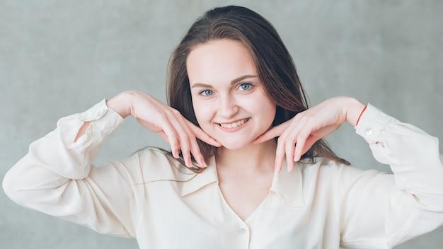 Pielęgnacja skóry i zębów. piękna młoda kobieta portret. kobieta uśmiechając się delikatnie dotykając jej twarzy.