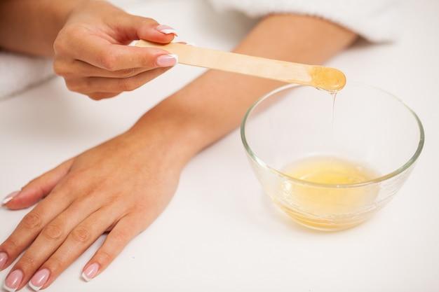Pielęgnacja skóry: kobieta nakłada wosk na dłoń, aby usunąć włosy.