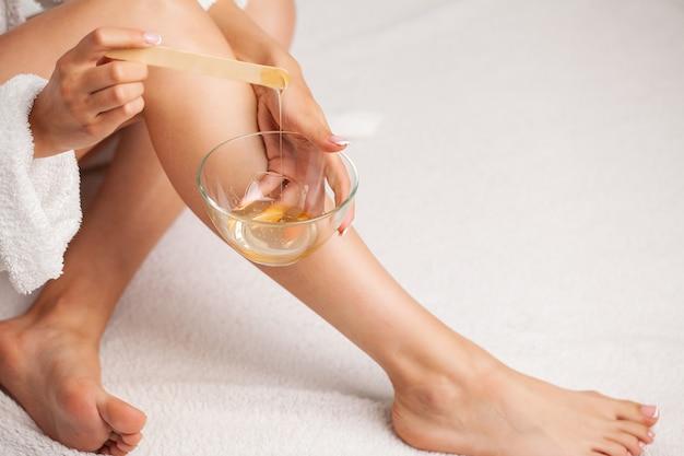 Pielęgnacja skóry: kobieta nakłada wosk na nogę, aby usunąć włosy.