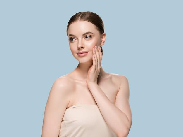 Pielęgnacja skóry kobieta rękami portret zbliżenie skóry kosmetycznych wiek koncepcja. kolor tła niebieski