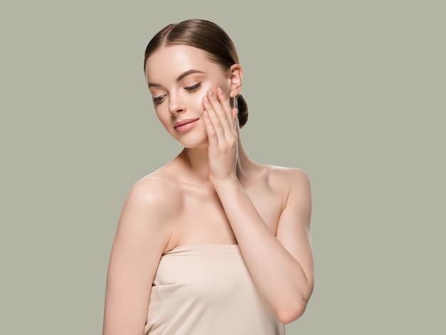 Pielęgnacja skóry kobieta rękami portret zbliżenie skóry kosmetycznych wiek koncepcja. kolor tła zielony