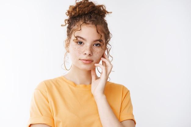 Pielęgnacja skóry, koncepcja moda delikatność. zmysłowa atrakcyjna ruda dziewczyna piegi kręcone hairbun nosić pomarańczowy t-shirt wygląd aparat dotykowy czysta delikatna skóra nakładanie produktu kosmetycznego, białe tło