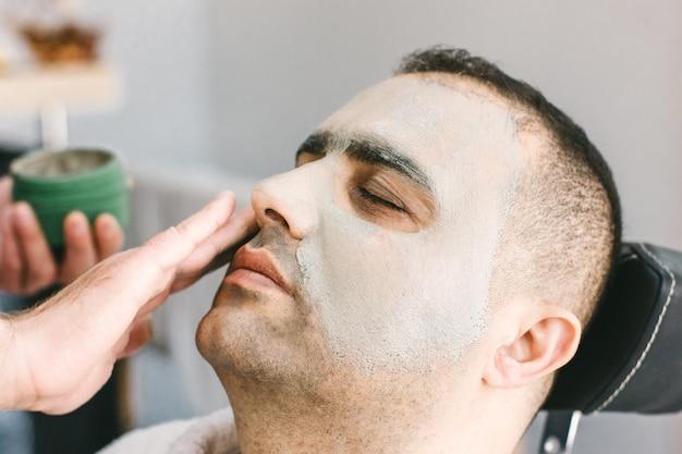 Pielęgnacja skóry męskiej w salonie kosmetycznym. nakładanie glinianej maski oczyszczającej na twarz mężczyzny