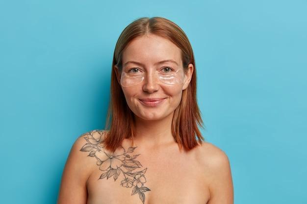 Pielęgnacja skóry oczu. zadowolona rudowłosa europejka nakłada przezroczyste łaty kolagenowe pod oczami ma idealnie gładki tatuaż na nagim ciele, lubi liftingujący zabieg przeciwzmarszczkowy w celu odmłodzenia