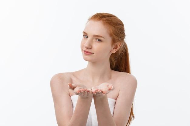 Pielęgnacja skóry piękna kobieta pokazując pustą dłoń z miejsca na kopię produktu