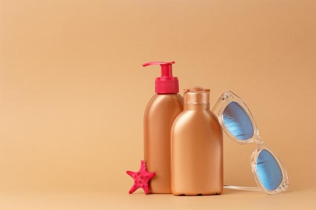 Pielęgnacja skóry twarzy i ciała na plaży, na morzu, podczas letnich wakacji. bezpieczny zestaw do opalania z okularami przeciwsłonecznymi różowymi i rozgwiazdowymi.