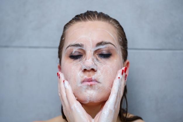 Pielęgnacja skóry twarzy. kobieta, stosując środek do mycia twarzy na zbliżenie twarzy. dziewczyna używa oczyszczającego produktu kosmetycznego na skórze, myjąc twarz na jasnym tle