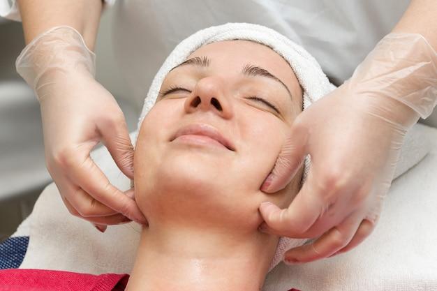 Pielęgnacja skóry twarzy. kosmetyczka nakładająca maseczkę olejową na twarz za pomocą pędzla w salonie spa