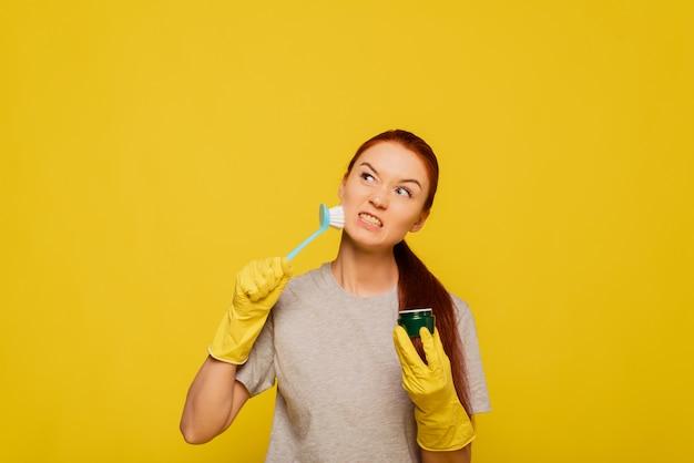 Pielęgnacja skóry twarzy. zbliżenie młoda kobieta w żółte rękawiczki i szczotki do czyszczenia w dłoni złuszczające skóry. portret pięknej zdrowej dziewczyny z naturalnego makijażu szorowanie skóry twarzy