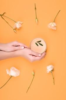 Pielęgnacja skóry za pomocą naturalnych kosmetyków. kobiece ręce trzymają słoik naturalnych kosmetyków. krem. eko kosmetyki. krem w dłoniach. ochrona skóry. miejsce na napis. leżał płasko
