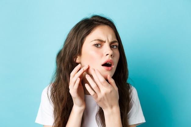 Pielęgnacja skóry zdjęcie zmartwionej nastolatki patrzącej w lustro i zauważającej pryszcz na twarzy, próbującej wycisnąć...