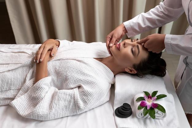 Pielęgnacja spa młoda kobieta wykonuje masaż twarzy leżąc na kanapie w elitarnym salonie.