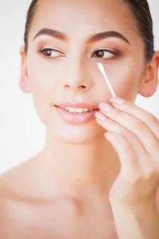Pielęgnacja twarzy. dziewczyna ze zdrową skórą, patrząc w lustro