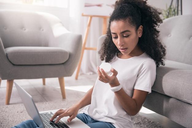 Pielęgnacja twarzy. przyjemna młoda kobieta, patrząc na butelkę kremu, siedząc z przodu, jeśli laptop