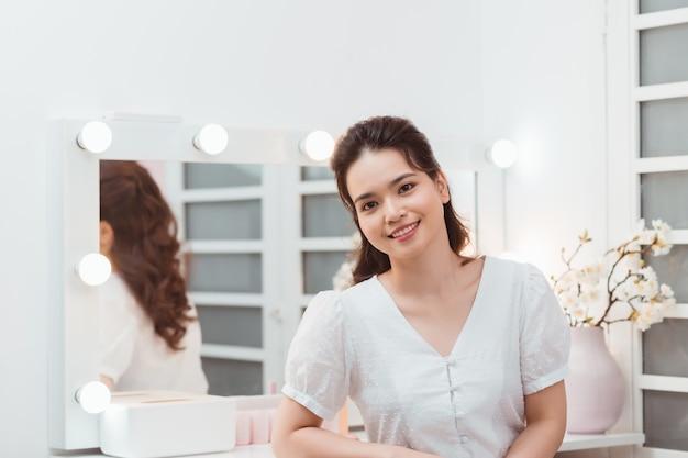 Pielęgnacja twarzy uroda kobiety. portret piękna szczęśliwa młoda kobieta ze świeżą zdrową skórą, patrząc w pobliżu lustra.