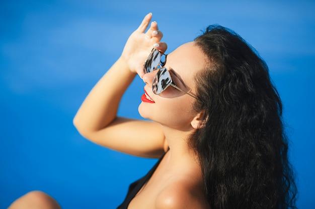 Pielęgnacja urody i ciała. zmysłowa młoda kobieta relaksuje w plenerowym zdroju pływackim basenie