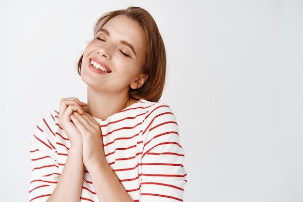 Pielęgnacja urody i skóry. szczęśliwa młoda kobieta z naturalnym jasnym makijażem, krótkie włosy, marząca o czymś słodkim, czule uśmiecha się i zamyka oczy, biała ściana