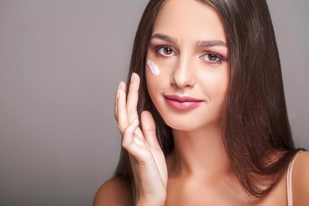Pielęgnacja urody skóry. piękna kobieta szczęśliwa stosowania kremu kosmetycznego na czystą twarz. portret zbliżenie zdrowe uśmiechnięte modelki z naturalnym makijażem, świeżą miękką czystą skórę stosując balsam nawilżający