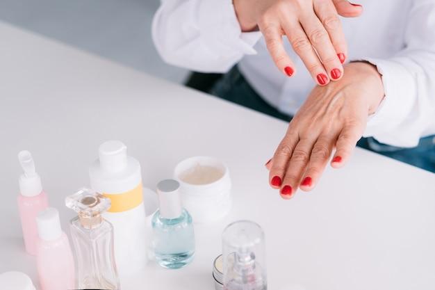 Pielęgnacja urody. starzejące się produkty do skóry dłoni. starsza pani stosująca drogie kosmetyki.