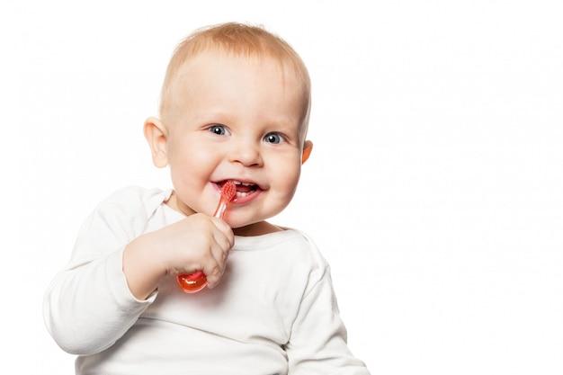 Pielęgnacja zębów dziecka. uśmiechnięta chłopiec szczotkuje jego zęby szczoteczką do zębów dla niemowlaka.