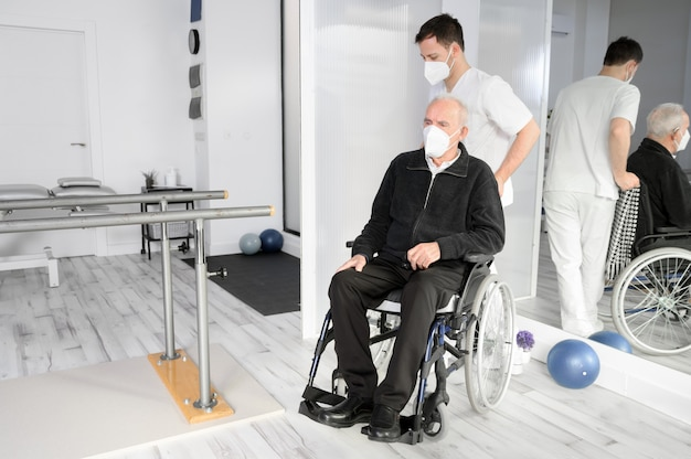 Pielęgniarka asystująca starszemu niepełnosprawnemu pacjentowi na wózku inwalidzkim w centrum rehabilitacji.