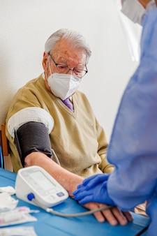 Pielęgniarka chroniona przed koronawirusem bierze mankiet do pomiaru ciśnienia krwi starszego mężczyzny