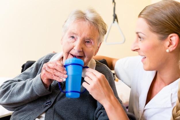 Pielęgniarka daje napój starsza kobieta w wózku inwalidzkim