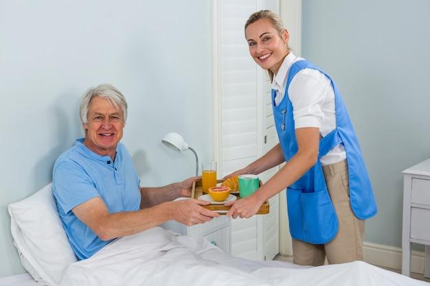 Pielęgniarka daje śniadanie do uśmiechniętego starszego mężczyzny