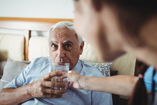 Pielęgniarka daje szklankę wody do starszego mężczyzny