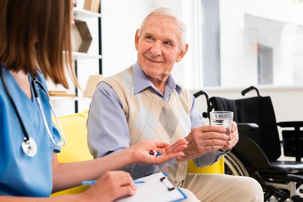 Pielęgniarka daje tabletki do uśmiechniętego starca