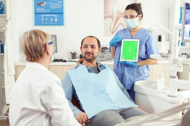 Pielęgniarka dentystyczna pokazująca zielony ekran starszemu lekarzowi stomatologii podczas badania bólu zęba pacjentowi siedzącemu na fotelu dentystycznym