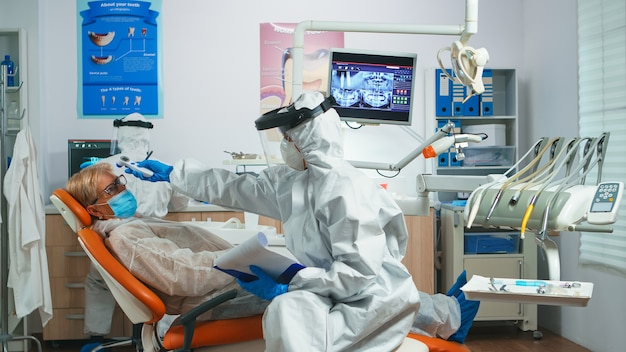 Pielęgniarka dentystyczna w kombinezonie ochronnym kontrolująca temperaturę pacjenta przed badaniem stomatologicznym podczas pandemii koronawirusa. koncepcja nowej normalnej wizyty u dentysty w epidemii koronawirusa w odzieży ochronnej