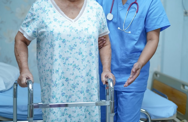 Pielęgniarka fizjoterapeuta opieka lekarz, pomoc i wsparcie starszy kobieta cierpliwy spacer z chodzikiem w szpitalu.