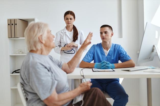 Pielęgniarka i lekarz słuchają pacjenta w gabinecie lekarskim