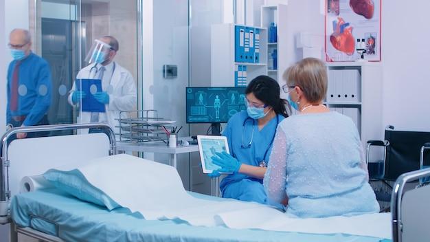 Pielęgniarka i lekarz z wyposażeniem ochronnym i maskami udzielają konsultacji lekarskiej podczas epidemii koronawirusa w nowoczesnej klinice. pacjent siedzi na szpitalnym łóżku i patrzy na tablet pc