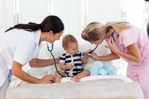 Pielęgniarka i pediatra zajmują się dzieckiem