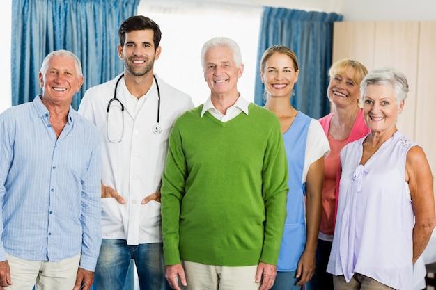 Pielęgniarka i seniorzy stojący razem