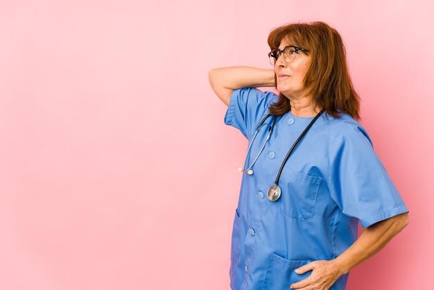 Pielęgniarka kaukaski średnim wieku kobieta na białym tle dotykając tyłu głowy, myślenia i dokonywania wyboru.