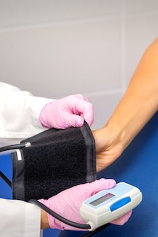 Pielęgniarka lub lekarz stawia tonometr na ramieniu młodej kobiety w szpitalu