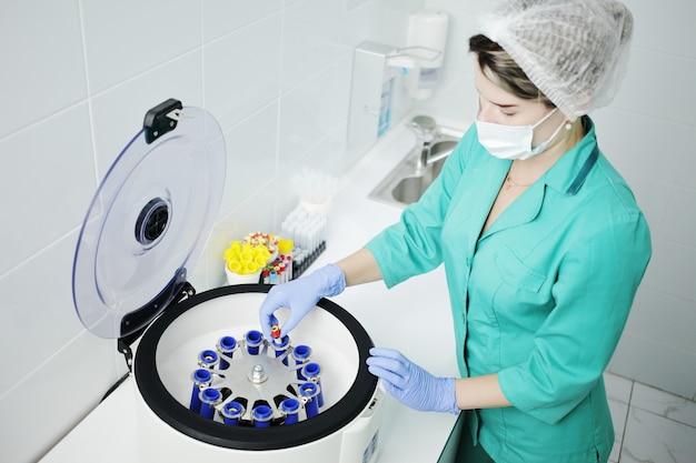 Pielęgniarka lub lekarz w masce medycznej trzyma probówkę do badania krwi. wirówka laboratoryjna do oddzielania składników krwi