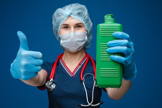 Pielęgniarka lub lekarz z butelką środka dezynfekującego i kciukiem do góry.