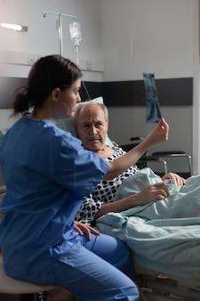 Pielęgniarka medyczna analizująca prześwietlenie klatki piersiowej starszego pacjenta w sali szpitalnej, omawiająca wyjaśnienie diagnozy