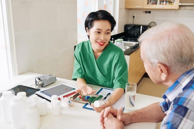 Pielęgniarka medyczna odwiedzająca starszego pacjenta