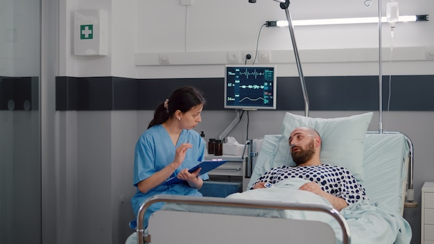 Pielęgniarka medyczna omawia leczenie choroby z hospitalizowanym chorym mężczyzną