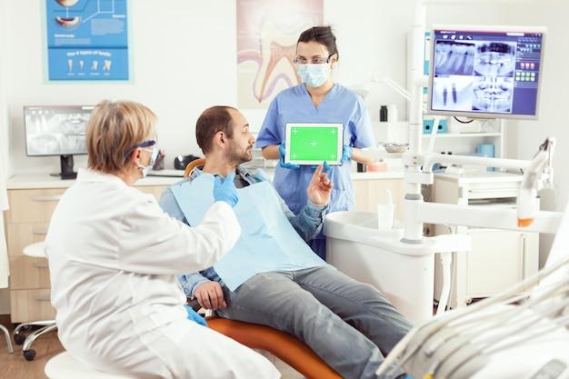 Pielęgniarka medyczna trzymająca makietę tabletu chroma-klucz z zielonym ekranem z izolowanym wyświetlaczem podczas konsultacji somatologicznej